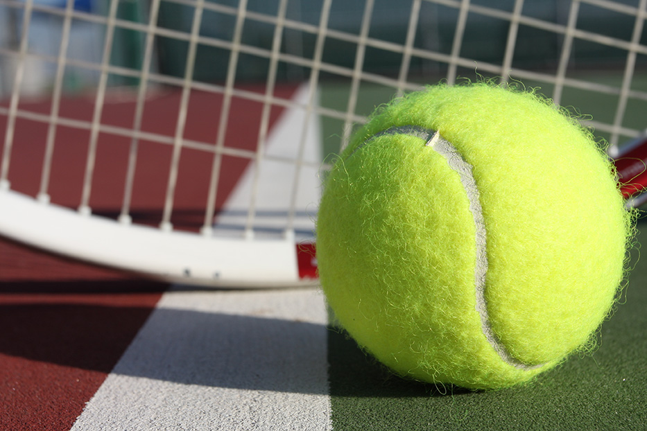 This tennis ball sits in front of a tennis racket on the court.