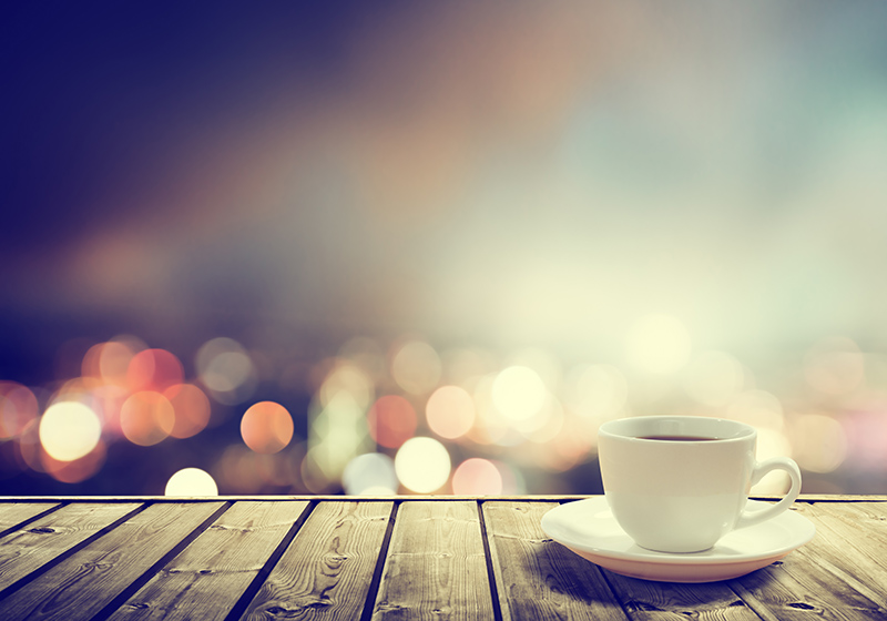 A cup of coffee with city lights in the background.